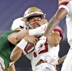 Florida State quarterback Jordan Travis (13) is tackled by a Miami player in the first quarter of an NCAA college football game Saturday, Sept. 26, 2020, in Miami Gardens, Fla. (Al Diaz/Miami Herald via AP)