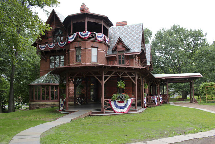 FILE - In this July 14, 2017 file photo, the Mark Twain House sits adorned with red, white and blue bunting in Hartford, Conn.  The historic home where Mark Twain and his family once lived has received a $1 million gift from bestselling novelist David Baldacci and his wife.  The Mark Twain House & Museum says the gift is expected to support new initiatives including writing programs and more appearances by authors.  (AP Photo/Pat Eaton-Robb, File)