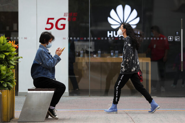 A woman wearing a face mask to help curb the spread of the coronavirus browses her smartphone as a masked woman walks by the Huawei retail shop promoting it 5G network in Beijing on Oct. 11, 2020. Chinese leaders are meeting to formulate an economic blueprint for the next five years that is expected to emphasize development of semiconductors and other technology amid a feud with Washington that is cutting off access to U.S. components for China's fledgling tech industries. (AP Photo/Andy Wong)