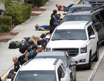FILE- In this Jan. 6, 2017 file photo, people take cover outside Fort Lauderdale–Hollywood International Airport, in Fort Lauderdale, Fla., after a shooter opened fire inside a terminal of the airport, killing several people and wounding others before being taken into custody. For Florida, the 2010s were a decade of high-profile mass shootings at a nightclub, high school, airport and naval base, leaving 74 victims dead.  (AP Photo/Wilfredo Lee, File)