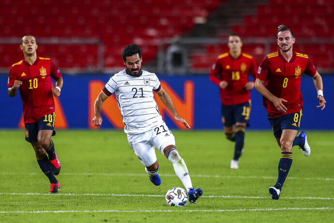 Germany's Ilkay Gundogan, center, runs with the ball past Spain's Thiago Alcantara, left, and Spain's Fabian Ruiz during their UEFA Nations League soccer match at the Mercedes-Benz Arena stadium in Stuttgart, Germany, Thursday, Sept. 3, 2020. (AP Photo/Matthias Schrader)