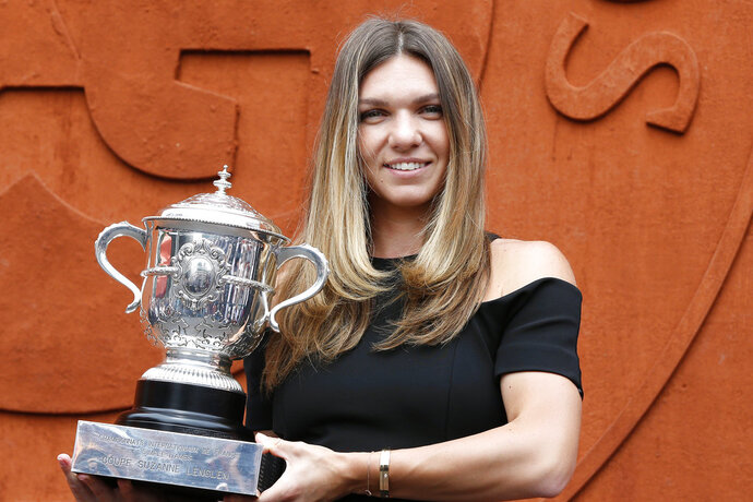 Romania's Simona Halep holds the cup at the Roland Garros stadium, Sunday, June 10, 2018 in Paris. Halep won Saturday the French Open tennis tournament women's final. (AP Photo/Thibault Camus)