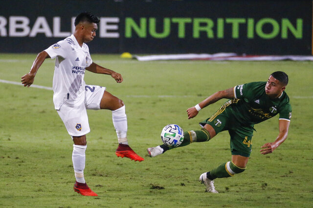 FILE - In this Oct. 7, 2020, file photo, LA Galaxy midfielder Efrain Álvarez (26) and Portland Timbers midfielder Marvin Loria (44) vie for the ball during an MLS soccer match in Carson, Calif.  Álvarez started for Mexico in last year's final of the Under-17 World Cup and is among several dual nationals at American training camp this week ahead of a Dec. 9 exhibition against El Salvador in Fort Lauderdale, Fla. U.S. coach Gregg Berhalter will try to persuade him and other dual nationals to commit to the U.S. program. (AP Photo/Ringo H.W. Chiu, File)