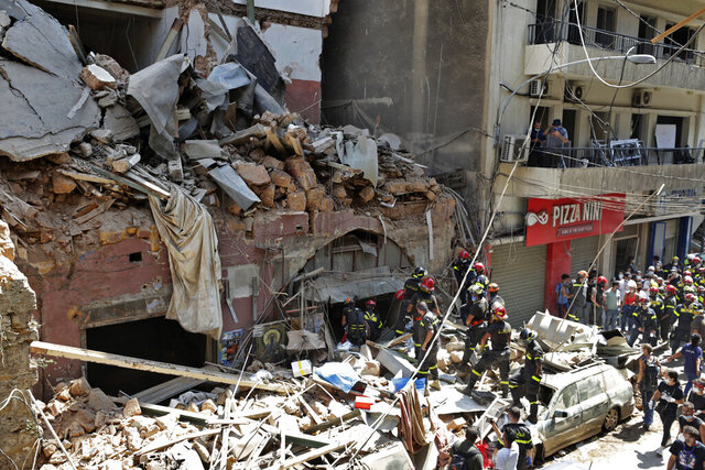 French and Lebanese firemen search in the rubble of a building after the Tuesday explosion at the seaport of Beirut, in Beirut, Lebanon, Thursday, Aug. 6, 2020. Lebanese officials targeted in the investigation of the massive blast that tore through Beirut sought to shift blame for the presence of explosives at the city's port, and the visiting French president warned that without serious reforms the country would