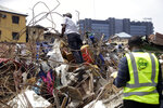 Government officials from Standard Organisation of Nigeria examine materials used in constructing the building that collapsed in Lagos, Nigeria, Thursday March 14, 2019. A Nigerian official says search efforts have been halted a day after a school building collapsed in Lagos with an unknown number of children inside.(AP Photo/Sunday Alamba)