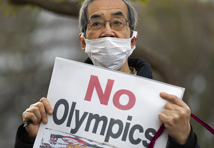 FILE - In this Feb. 12, 2021, file photo, a demonstrator holds a sign protesting the planned Tokyo 2020 Olympic games near a building where Yoshiro Mori was meeting to announce his resignation as the president of the Tokyo Olympic Organizing Committee in Tokyo. Mori stepped down two months ago after making derogatory comments about women. (AP Photo/Hiro Komae, File)