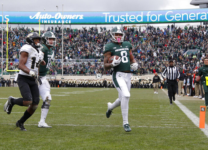 Michigan State's Jalen Nailor (8) scores a touchdown against Purdue's Antonio Blackmon (14) as Michigan State quarterback Rocky Lombardi, left rear, trails during the fourth quarter of an NCAA college football game, Saturday, Oct. 27, 2018, in East Lansing, Mich. (AP Photo/Al Goldis)