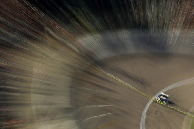 In this photo taken with a slow shutter, Chase Elliott races during a NASCAR Cup Series auto race at Kansas Speedway in Kansas City, Kan. Sunday, Oct. 20, 2019. Elliott placed second. (AP Photo/Charlie Riedel)