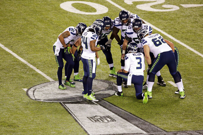 FILE - In this Feb. 2, 2014, file photo, Seattle Seahawks' Russell Wilson (3) huddles with his team during the first half of the NFL Super Bowl XLVIII football game against the Denver Broncos in East Rutherford, N.J. The average experience on Seattle's 2013 Super Bowl champions was 3.66 years. Seattle returned to the Super Bowl the next season, but went into a rebuilding mode not long after, with many of the top contributors from the Super Bowl teams becoming too pricey, and a scramble ensuing to put fresh talent around still-young quarterback, Wilson. (AP Photo/Charlie Riedel, File)
