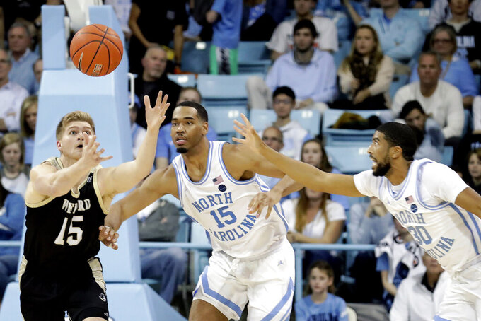 Wofford's Trevor Stumpe (15) battles North Carolina's Garrison Brooks (15) and K.J. Smith (30) for the ball during the second half of an NCAA college basketball game in Carmichael Arena in Chapel Hill, N.C., Sunday, Dec. 15, 2019. (AP Photo/Chris Seward)