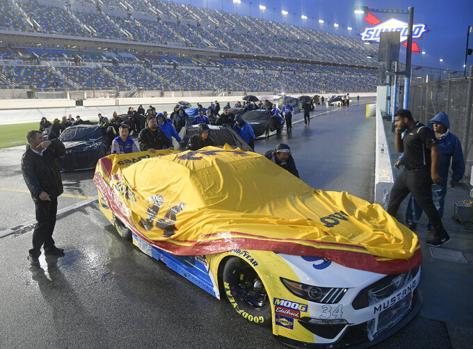 Michael McDowell's crew pushes his car back to the garages after the NASCAR Cup Series auto race was postponed because of inclement weather at Daytona International Speedway, Saturday, July 6, 2019, in Daytona Beach, Fla. (AP Photo/Phelan Ebenhack)