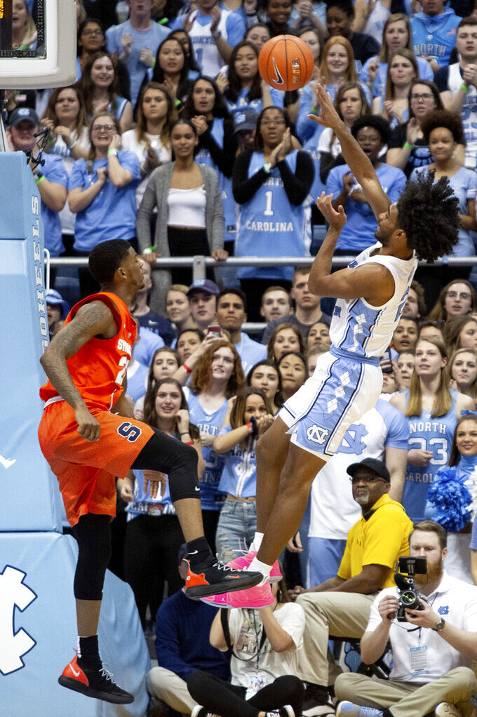 North Carolina's Coby White, right, attempts a shot over Syracuse's Frank Howard, left, during the second half of an NCAA college basketball game in Chapel Hill, N.C., Tuesday, Feb. 26, 2019.  White had a season-high 34 points as No. 5 North Carolina defeated Syracuse 93-85. (AP Photo/Ben McKeown)