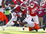 Oklahoma running back Trey Sermon (4) scramble to escape a tackle by Oklahoma State linebacker Calvin Bundage (1) in the first quarter of an NCAA college football game in Norman, Okla., Saturday, Nov. 10, 2018. (AP Photo/Alonzo Adams)