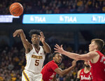 Minnesota guard Marcus Carr (5) passes the ball away from Nebraska guard Thorir Thorbjarnarson (34) in the first half of an NCAA college basketball game Sunday, March 8, 2020, in Minneapolis. (Jerry Holt/Star Tribune via AP)