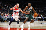 Milwaukee Bucks forward Khris Middleton, right, drives against Washington Wizards guard Garrison Mathews in the second half of an NBA preseason basketball game, Sunday, Oct. 13, 2019, in Washington. (AP Photo/Patrick Semansky)