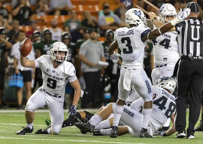 Utah State linebacker David Woodward (9) holds up the football after intercepting a pass in the first half of an NCAA college football game, Saturday, Nov. 3, 2018, in Honolulu. Utah State safety Jontrell Rocquemore (3) signals his team has position of the football. (AP Photo/Eugene Tanner)