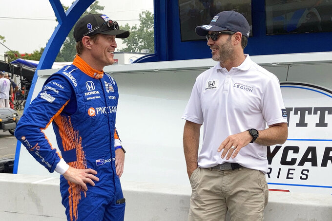 Six-time IndyCar champion Scott Dixon, left, chats with Chip Ganassi Racing teammate Jimmie Johnson before the start of practice of the IndyCar auto race, Friday, Aug. 6, 2021, in Nashville, Tenn. (AP Photo/Dan Gelston)