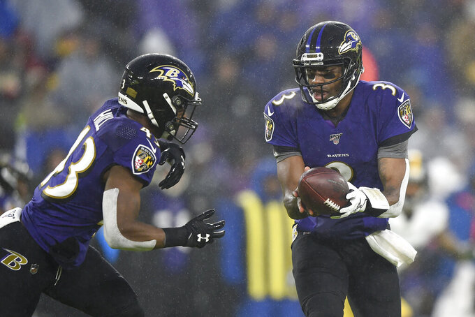 Baltimore Ravens quarterback Robert Griffin III (3) hands off to running back Justice Hill (43) during the first half of an NFL football game against the Pittsburgh Steelers, Sunday, Dec. 29, 2019, in Baltimore. (AP Photo/Gail Burton)
