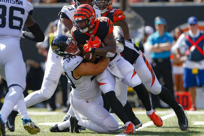 Cincinnati Bengals running back Joe Mixon (28) is tackled by Jacksonville Jaguars defensive tackle Taven Bryan (90) in the first half of an NFL football game, Sunday, Oct. 20, 2019, in Cincinnati. (AP Photo/Gary Landers)