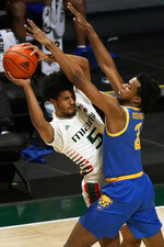 Miami guard Harlond Beverly (5) attempts to pass past Pittsburgh guard Femi Odukale (2) during the first half of an NCAA college basketball game, Wednesday, Dec. 16, 2020, in Coral Gables, Fla. (AP Photo/Wilfredo Lee)