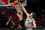 San Antonio Spurs center Jakob Poeltl, right, blocks the shot of Portland Trail Blazers center Enes Kanter, left, during the second half of an NBA basketball game in Portland, Ore., Monday, Jan. 18, 2021. (AP Photo/Steve Dykes)