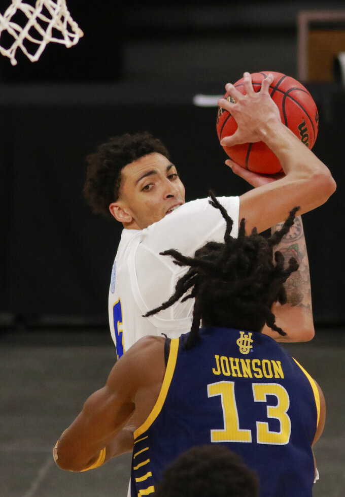 UC Santa Barbara's Miles Norris (5) keeps the ball away from UC Irvine's Austin Johnson (13) during the second half of an NCAA college basketball game for the championship of the Big West Conference men's tournament Saturday, March 13, 2021, in Las Vegas. UC Santa Barbara won 79 to 63. (AP Photo/Ronda Churchill)