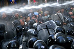 Police use a water cannon against demonstrators gathered at the Georgian parliament building in Tbilisi, Georgia, Monday, Nov. 18, 2019.Police in riot gear in the country of Georgia are trying to push thousands of demonstrators away from the parliament building in the capital on the second day of sizeable protests over the failure of promised election reforms. (AP Photo/Zurab Tsertsvadze)