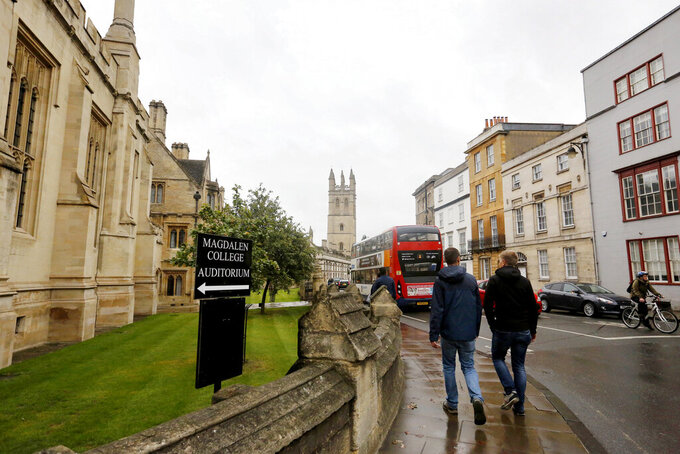 """FILE - In this Sunday, Sept. 3, 2017 file photo, people walk around Oxford University's campus in Oxford, England. On Friday, April 2, 2021, The Associated Press reported on stories circulating online incorrectly asserting Oxford is considering removing sheet music from its music curriculum as part of sweeping changes intended to """"decolonize"""" the program. But there are no plans under consideration to remove sheet music or western musical notation from the music curriculum at Oxford University, according to Stephen Rouse, head of university communications. Rouse told The Associated Press that while the music faculty is planning to expand its music curriculum to broaden offerings, cutting sheet music is not part of the plan. (AP Photo/Caroline Spiezio)"""