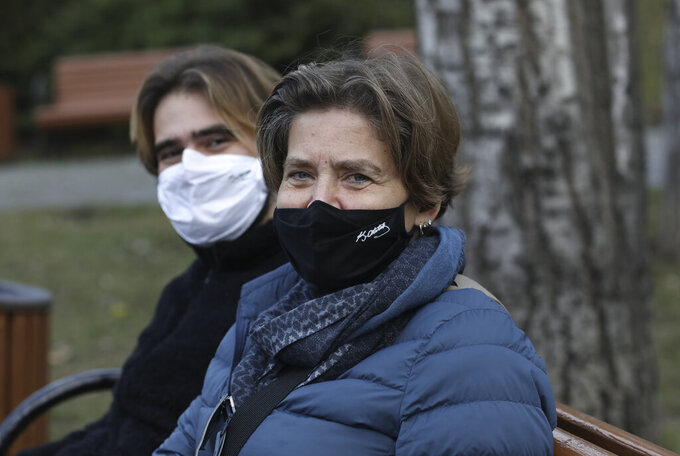 A Turkish mother and her son wearing masks with the signatures of Turkey's founder Mustafa Kemal Ataturk to help protect against the spread of coronavirus, sit in a deserted public garden during a lockdown, in Ankara, Turkey, Saturday, Jan. 9, 2021. Turkey impose a two-day lockdown on the weekend, in a bid to stem the spread of COVID-19.(AP Photo/Burhan Ozbilici)