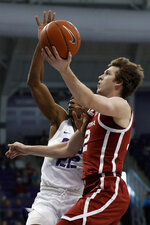 Oklahoma guard Austin Reaves (12) goes up for a shot in front of TCU guard RJ Nembhard (22) in the first half of an NCAA college basketball game in Fort Worth, Texas, Saturday, March 7, 2020. (AP Photo/Tony Gutierrez)