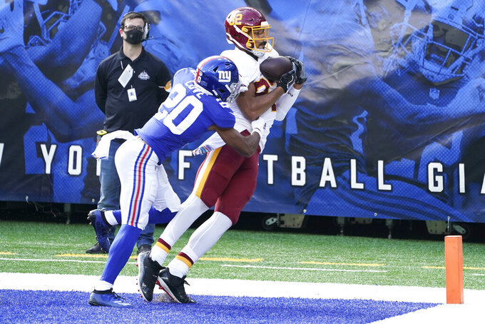 Washington Football Team's Logan Thomas (82) catches a pass for a touchdown in front of New York Giants' Julian Love (20) during the first half of an NFL football game Sunday, Oct. 18, 2020, in East Rutherford, N.J. (AP Photo/John Minchillo)