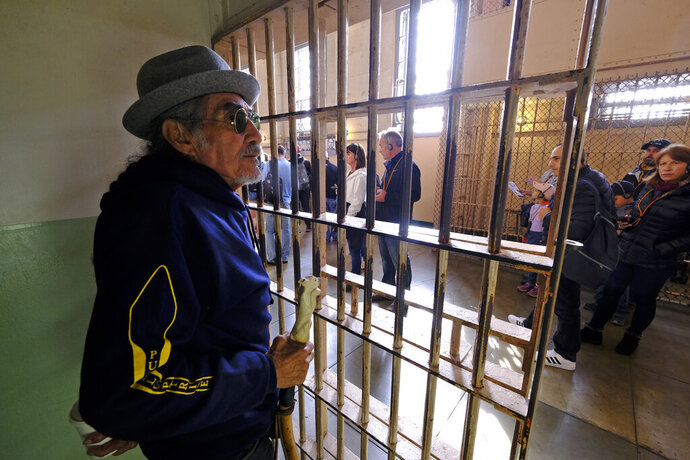 In this photo taken Tuesday, Nov. 12, 2019, Eloy Martinez, who took part in the Native American occupation of Alcatraz 50 years earlier, stands in the cell that he used to sleep in and looks out at tourists visiting the island in San Francisco. The week of Nov. 18, 2019, marks 50 years since the beginning of a months-long Native American occupation at Alcatraz Island in the San Francisco Bay. The demonstration by dozens of tribal members had lasting effects for tribes, raising awareness of life on and off reservations, galvanizing activists and spurring a shift in federal policy toward self-determination. (AP Photo/Eric Risberg)