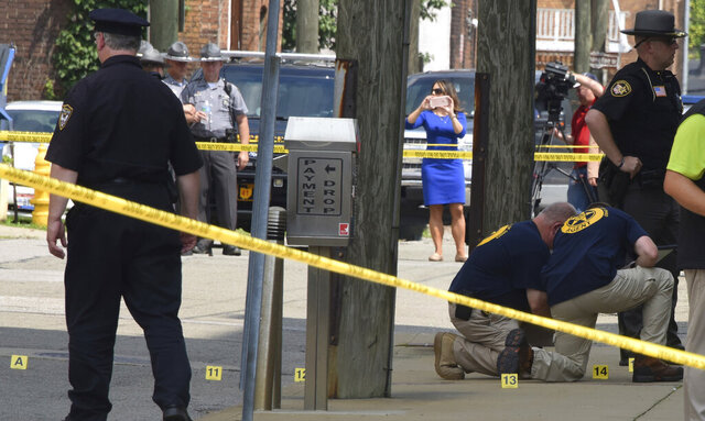 FILE - In this Monday Aug. 21, 2017 file photo shows evidence markers being placed on N. Court Street and the sidewalk next to the Jefferson County Courthouse in Steubenville, Ohio, after Jefferson County Judge Joseph Bruzzese Jr. was ambushed and shot earlier in the day. The Ohio Supreme Court has ruled that security camera footage of the judge being shot and wounded is a public record. The court's Tuesday, Nov. 24, 2020 ruling sided with arguments by The Associated Press in seeking access to the video. (Darrell Sapp/Pittsburgh Post-Gazette via AP)