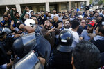 Hezbollah supporters clash with Lebanese riot policemen during a protest in Beirut, Lebanon, Tuesday, Oct. 29, 2019. Beirut residents have scuffled with Lebanese protesters blocking a main thoroughfare, prompting riot police to move to separate them. The tension Tuesday comes on the 13th day of anti-government protests. (AP Photo/Bilal Hussein)