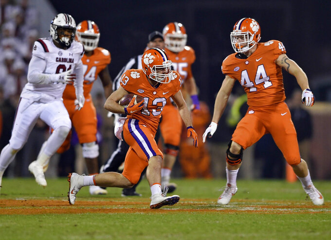 Clemson's Hunter Renfrow (13) rushes while pursued by South Carolina's Shameik Blackshear (91) with blocking help from Garrett Williams (44) during the first half of an NCAA college football game Saturday, Nov. 24, 2018, in Clemson, S.C. (AP Photo/Richard Shiro)