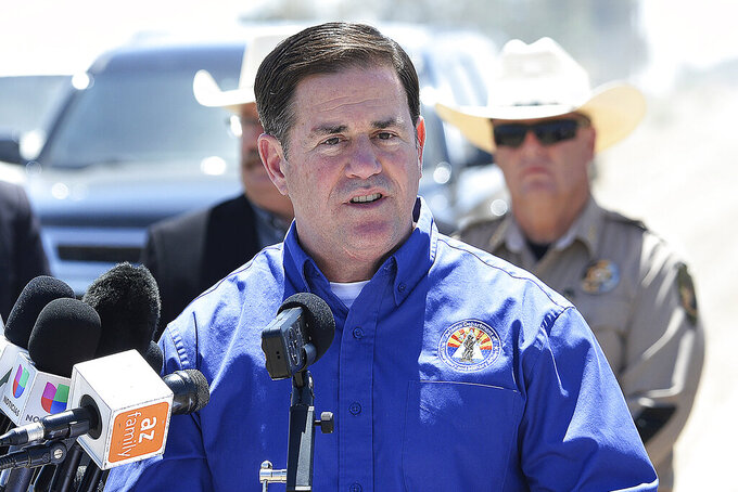 FILE - In this April 21, 2021, file photo, Arizona Gov. Doug Ducey addresses the media at the U.S-Mexico border in Yuma, Ariz. Ducey on Thursday, May 13, 2021, joined a growing number of Republican governors who are stopping payment of an extra $300 per week in pay for unemployed workers paid for by a federal virus relief package to force people to return to work. (Randy Hoeft/The Yuma Sun via AP, File)