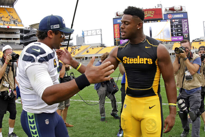 Seattle Seahawks quarterback Russell Wilson, left, greets Pittsburgh Steelers wide receiver JuJu Smith-Schuster after an NFL football game in Pittsburgh, Sunday, Sept. 15, 2019. The Seahawks won 28-26. (AP Photo/Gene J. Puskar)