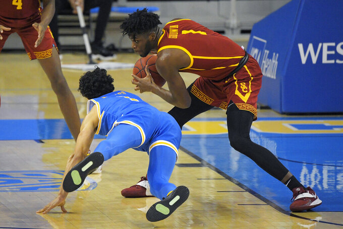 Southern California forward Chevez Goodwin, right, steals the ball from UCLA guard Jules Bernard during the first half of an NCAA college basketball game Saturday, March 6, 2021, in Los Angeles. (AP Photo/Mark J. Terrill)