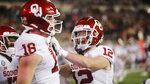 Oklahoma's Austin Stogner celebrates a touchdown catch with Drake Stoops during the first half of the team's NCAA college football game against Texas Tech on Saturday, Oct. 31, 2020, in Lubbock, Texas. (AP Photo/Mark Rogers)