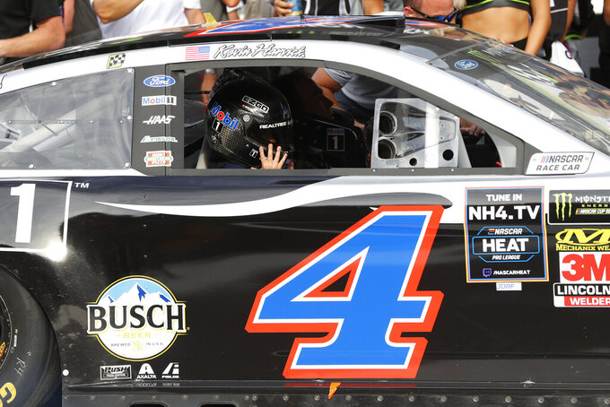 Kevin Harvick celebrates with his son, Keelan, wears his dad's helmet after a NASCAR Cup Series auto race at Michigan International Speedway in Brooklyn, Mich., Sunday, Aug. 11, 2019. (AP Photo/Paul Sancya)