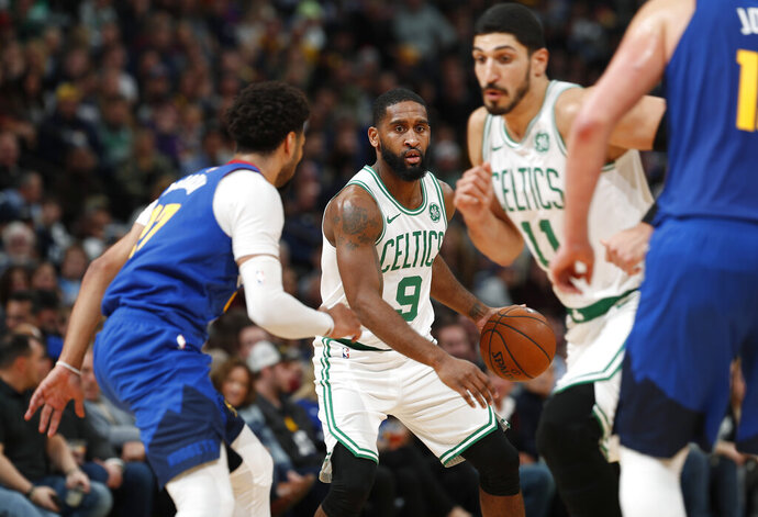 Boston Celtics guard Brad Wanamaker, center, looks to pass the ball to center Enes Kanter, right, as Denver Nuggets guard Jamal Murray drops back to defend during the second half of an NBA basketball game Friday, Nov. 22, 2019, in Denver. The Nuggets won 96-92. (AP Photo/David Zalubowski)