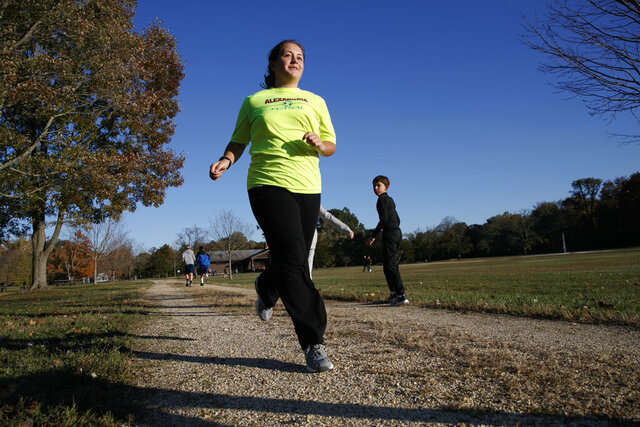 Grace Brown, 14, poses for a portrait while jogging at the park where she does her jogging workouts for her