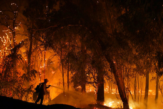 FILE - In this Oct. 31, 2019, file photo, a firefighter battles the Maria Fire in Somis, Calif. Since leaders first started talking about tackling the problem of climate change, the world has spewed more heat-trapping gases, gotten hotter and suffered hundreds of extreme weather disasters. Fires have burned, ice has melted and seas have grown. (AP Photo/Marcio Jose Sanchez, Fire)