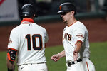 San Francisco Giants' Alex Dickerson, right, is congratulated by Evan Longoria (10) after scoring on a sacrifice fly by Brandon Crawford during the fifth inning against the Colorado Rockies in a baseball game Wednesday, Sept. 23, 2020, in San Francisco. (AP Photo/Tony Avelar)