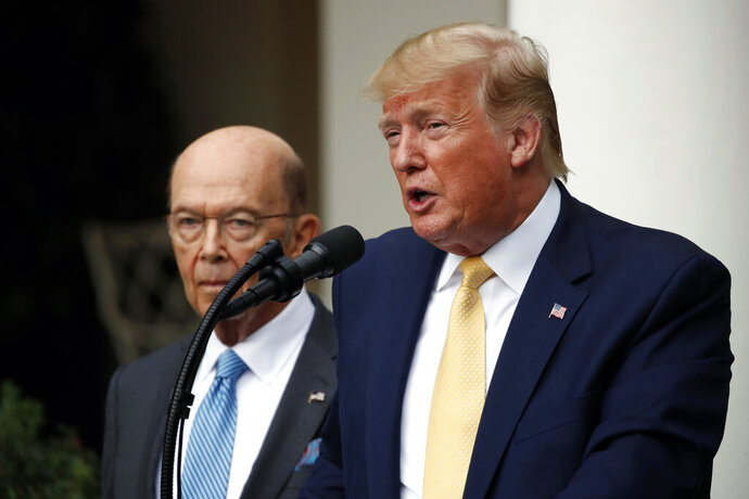 President Donald Trump is joined by Commerce Secretary Wilbur Ross as he speaks in the Rose Garden at the White House in Washington, Thursday, July 11, 2019. (AP Photo/Alex Brandon)