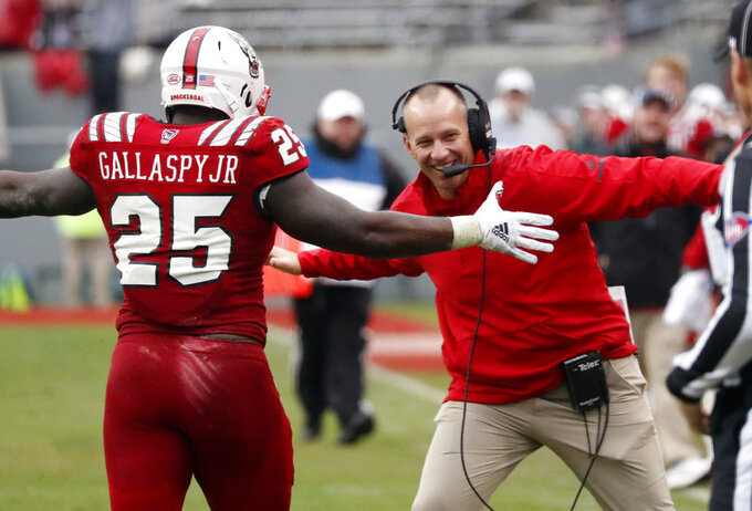 North Carolina State's Reggie Gallaspy II (25) is congratulated by head coach Dave Doeren after he ran for a long gain during the second half of NCAA college football game in Raleigh, N.C., Saturday, Dec. 1, 2018. (AP Photo/Chris Seward)