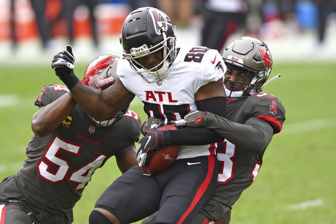 Atlanta Falcons wide receiver Laquon Treadwell (80) is stopped by Tampa Bay Buccaneers inside linebacker Lavonte David (54) and free safety Jordan Whitehead (33) during the first half of an NFL football game Sunday, Jan. 3, 2021, in Tampa, Fla. (AP Photo/Jason Behnken)