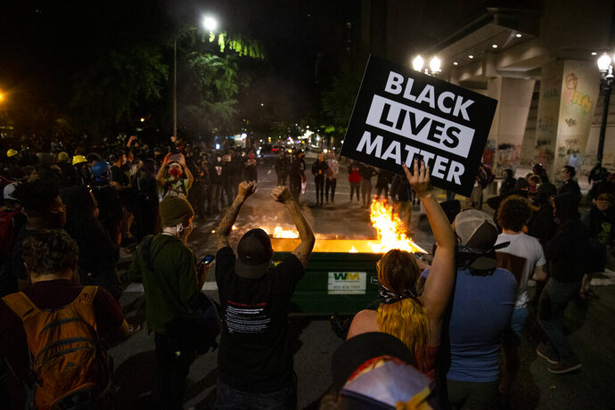 CORRECTS DAY AND DATE TO FRIDAY JULY 10. - FILE - In this Friday, July 10, 2020 file photo, a waste receptacle's contents are in flames as protesters gather in downtown Portland, Ore. The mayor of Portland, Oregon said late Sunday the U.S. Marshals Service are investigating the injury of a protester who was hospitalized in critical condition over the weekend after being hit in the head by an impact weapon fired by a federal law enforcement officer. Mayor Ted Wheeler said he spoke with with U.S. Attorney for Oregon Billy J. Williams and learned of the investigation. (Dave Killen/The Oregonian via AP, File)