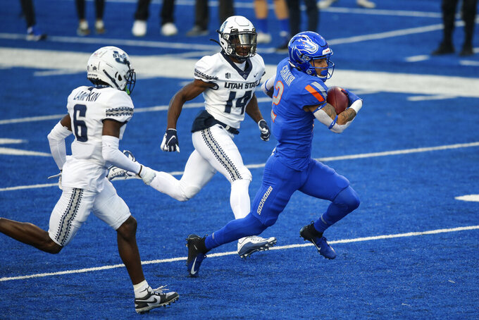 Boise State wide receiver Khalil Shakir (2) splits the Utah State defense of Utah State cornerback Zahodri Jackson (14) and Utah State cornerback Cam Lampkin (6) for a 52-yard touchdown reception in an NCAA college football game Saturday, Oct. 24, 2020, in Boise, Idaho. (AP Photo/Steve Conner)