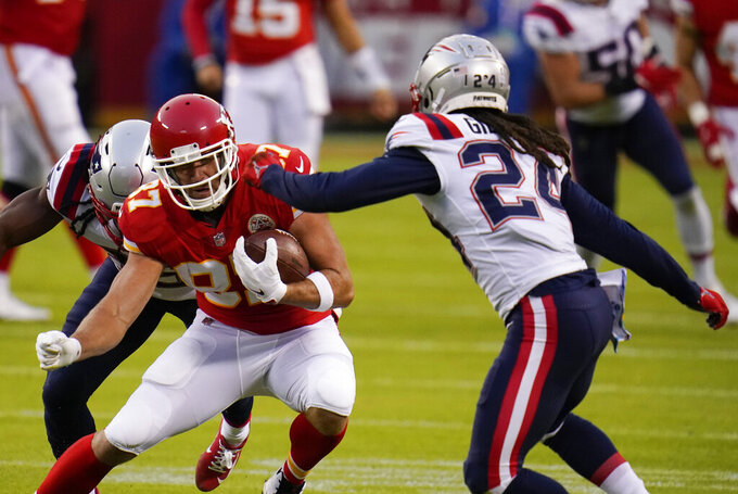 Kansas City Chiefs tight end Travis Kelce (87) runs from New England Patriots safety Kyle Dugger, left, and cornerback Stephon Gilmore, right, after catching a pass during the first half of an NFL football game, Monday, Oct. 5, 2020, in Kansas City. (AP Photo/Jeff Roberson)